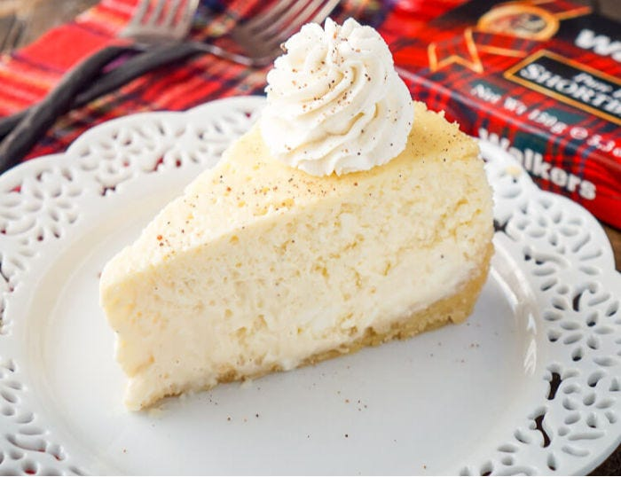 A slice of eggnog cheesecake with a box of shortbread cookies in the background.