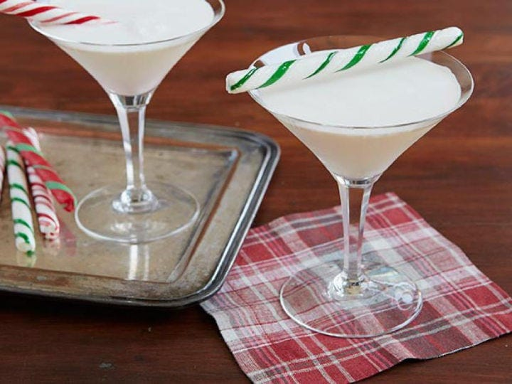 Two martini glasses filled with Candy Cane cocktails and peppermint stick garnishes.