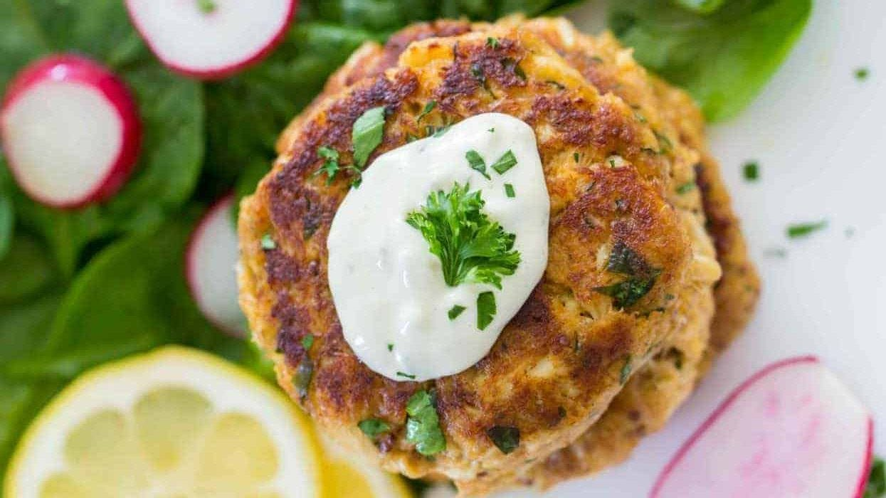A crab cake stack from with tartar sauce and chopped parsley on top.