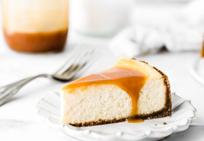 A slice of salted caramel cheese cake topped with a caramel sauce that is dripping over the side of the freshly sliced cake.