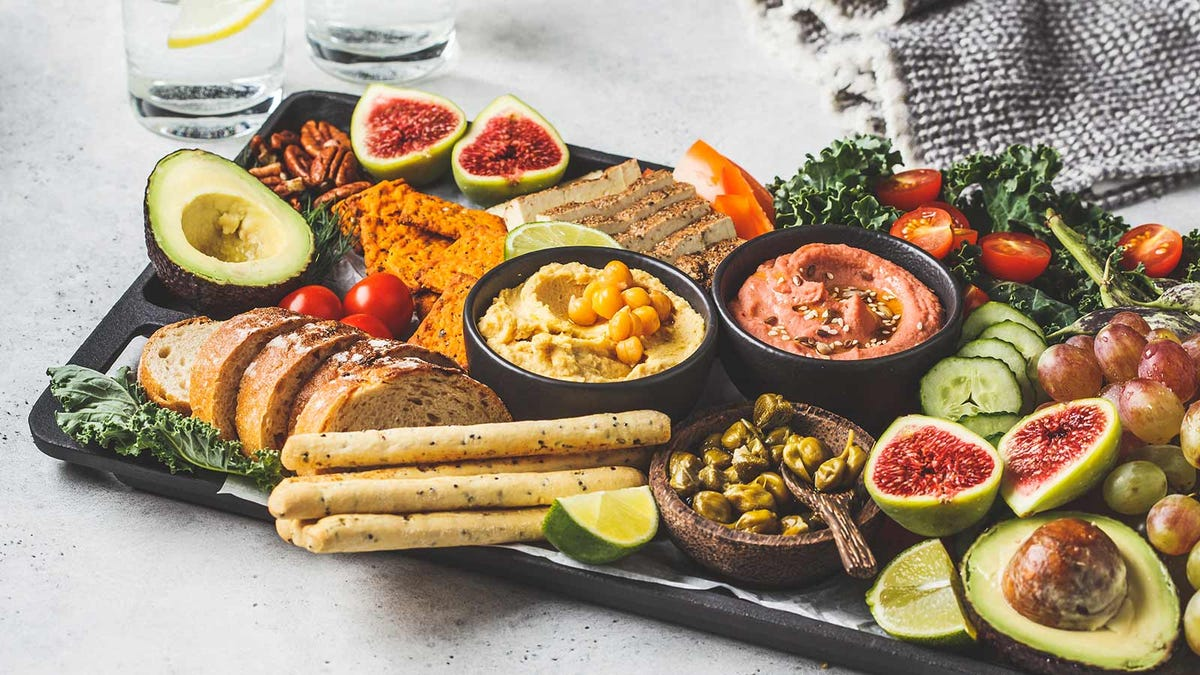 A delicious snack board loaded with fruits, vegetables, and breads.