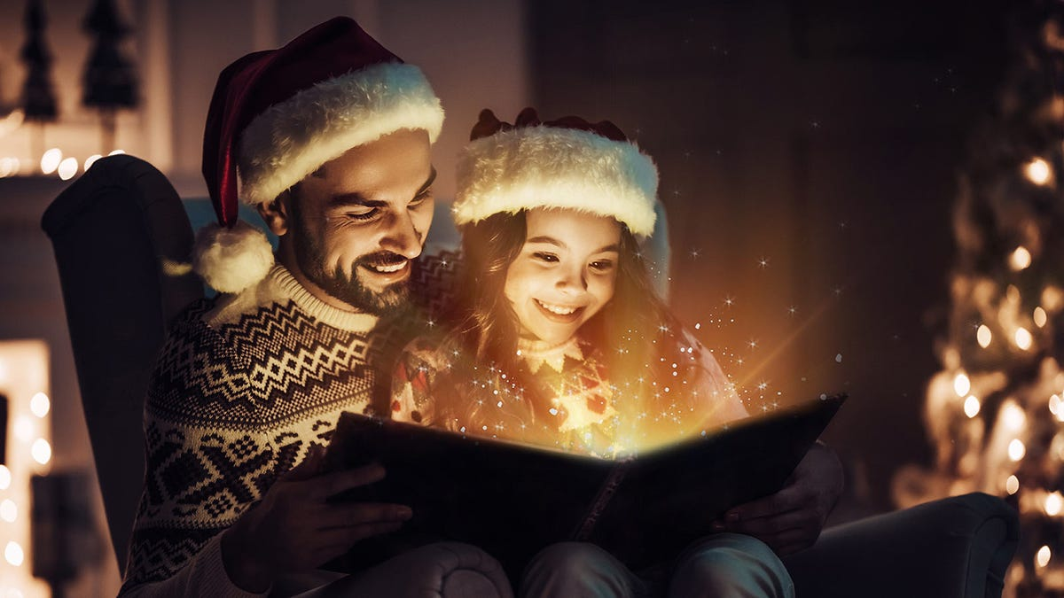 Man reading a magical Christmas book to a young girl, both are wearing Santa hats.