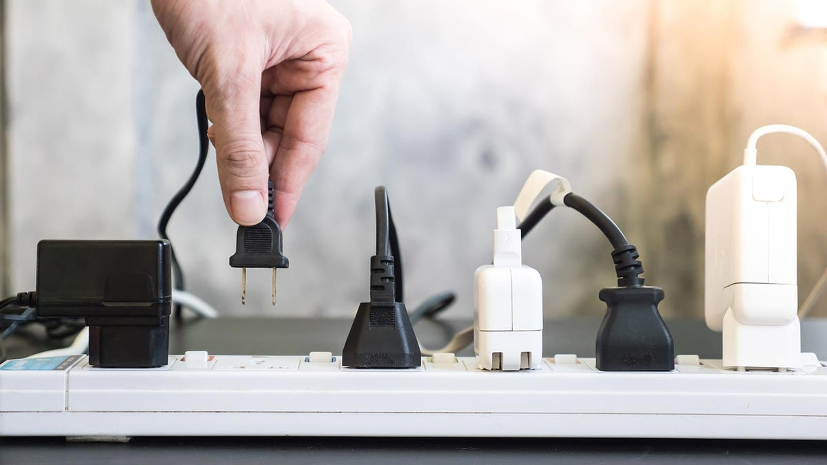 Man unplugging a cord from a power strip to save electricity.