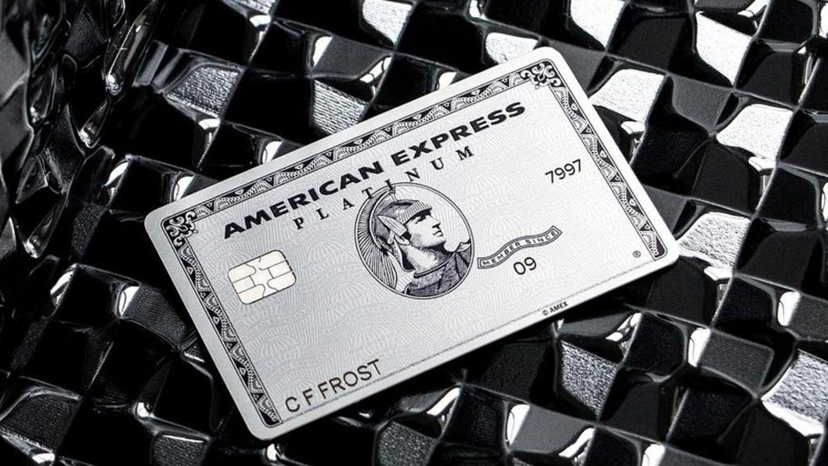 a metal body American Express Platinum card resting on a highly textured table.