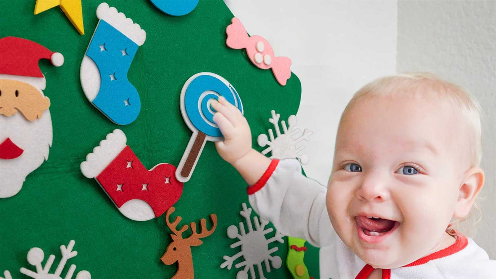 A toddler pulling on a felt ornament stuck to a flat felt Christmas tree hanging on the wall.