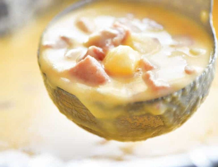 A closeup view of a ladle filled with creamy ham and cheese soup.
