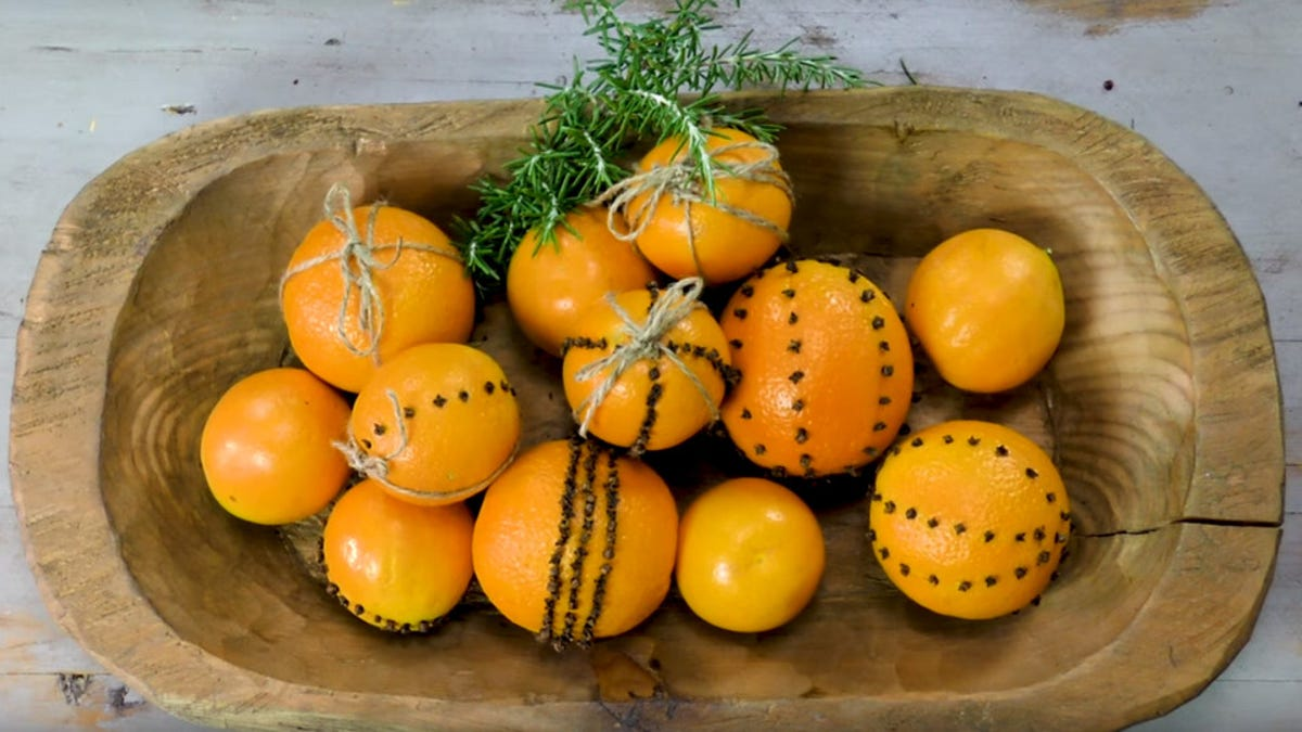 A bowl of pomanders arranged with some fragrant herbs.