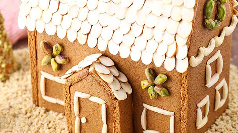 A gingerbread house decorated with slivered almonds to simulate shingles