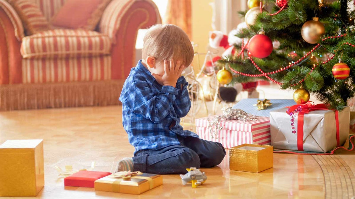 Upset little boy crying in front of a Christmas tree.