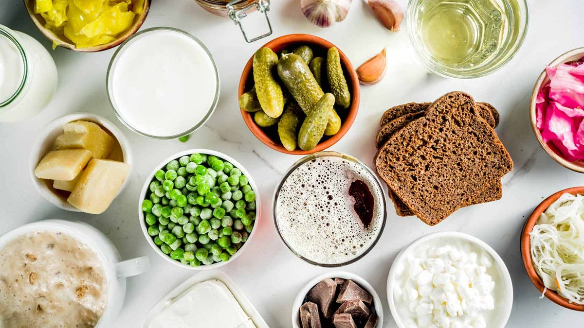 A variety of pro- and prebiotic foods like fresh vegetables and fermented products, laid out on a table.