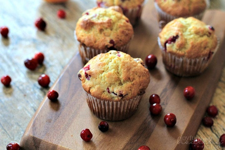 Five cranberry-orange muffins sitting on a cutting board surrounded by cranberries.