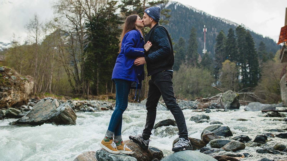 A man and woman kissing as they stand on rocks in a river.