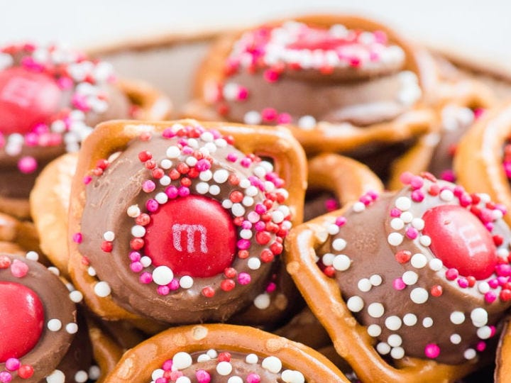 A pile of pretzels covered with Rolo candies, red M&M's, and sprinkles.