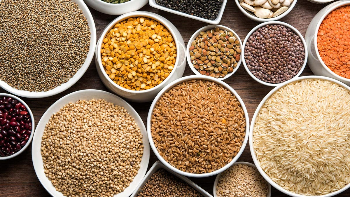 Bowls of grains and seeds on a table.