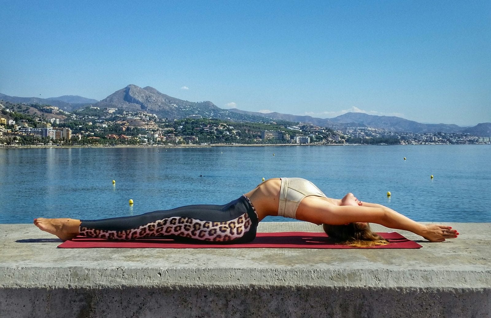 woman doing fish pose yoga in front ot sea