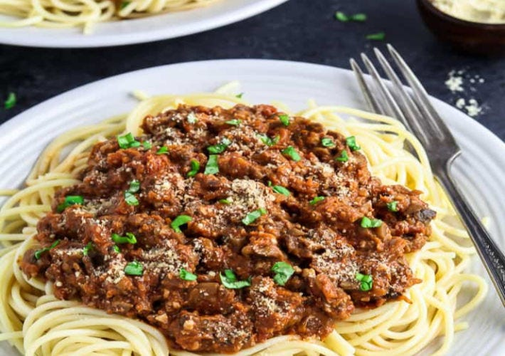 A plate of spaghetti pasta topped with vegan bolognese sauce all on a white plate with a fork on the side.