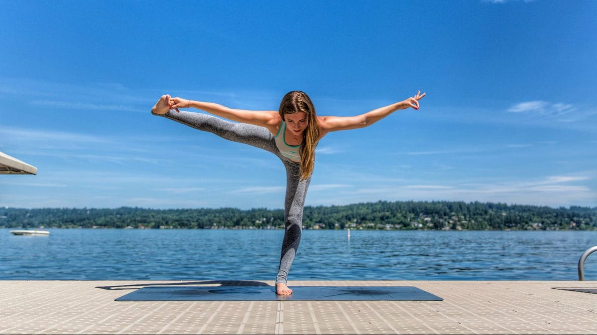 A woman doing a Yoga pose on a dock by the water.
