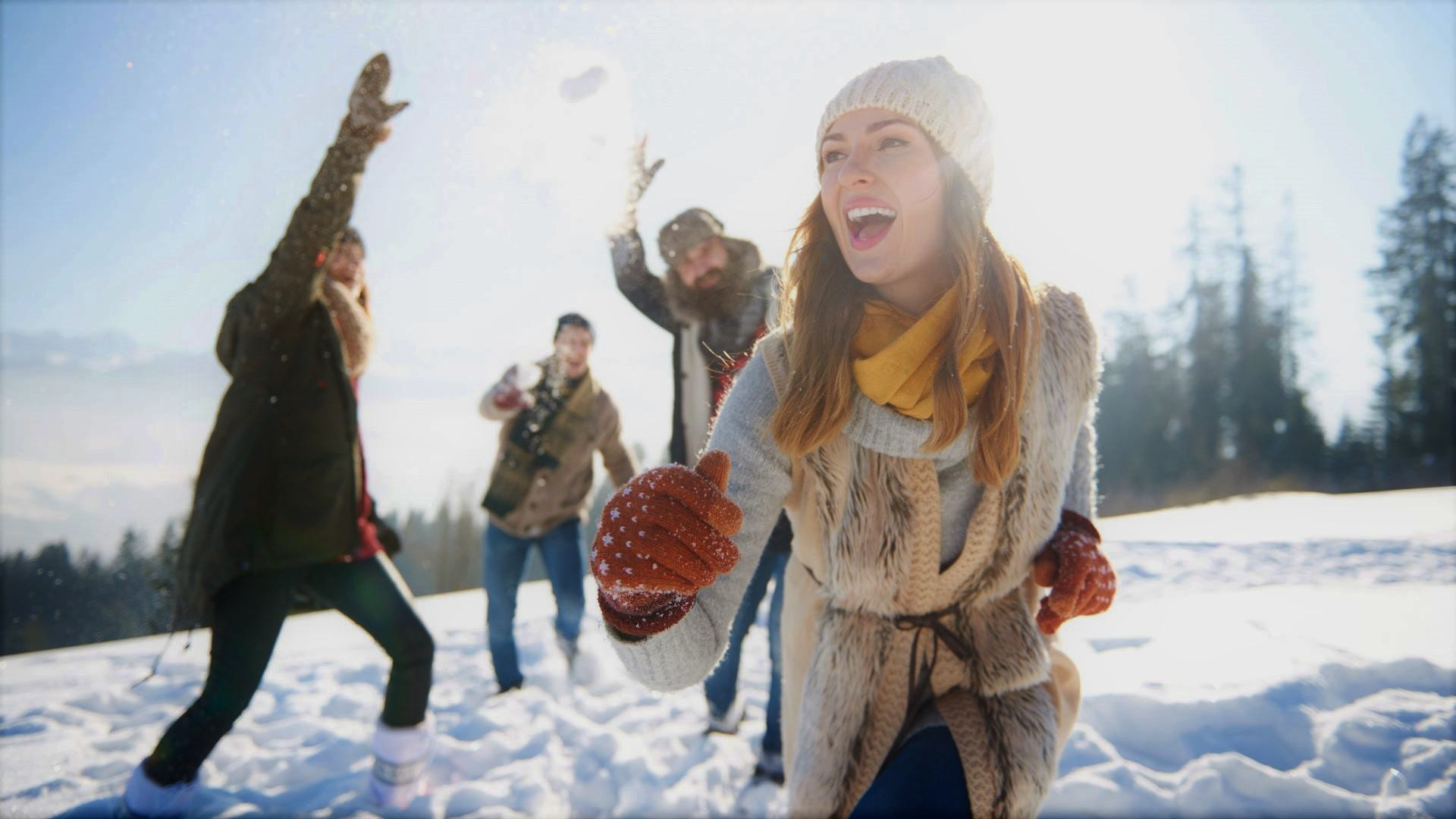 A woman and three men having a snowball fight.