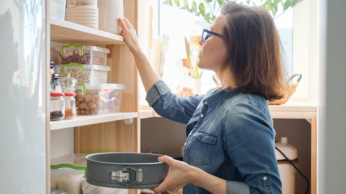 Woman putting things away in her organized pantry.