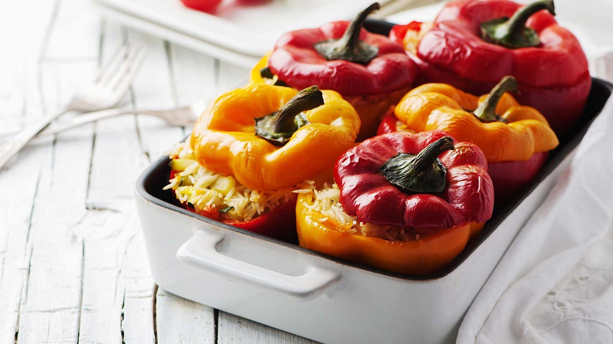 A cast iron casserole dish filled with stuffed bell peppers.