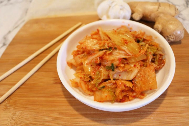 Kimchi served in a small bowl with chopsticks and ginger and garlic in the back.