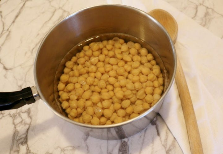 A pan full of chickpeas soaking in water.