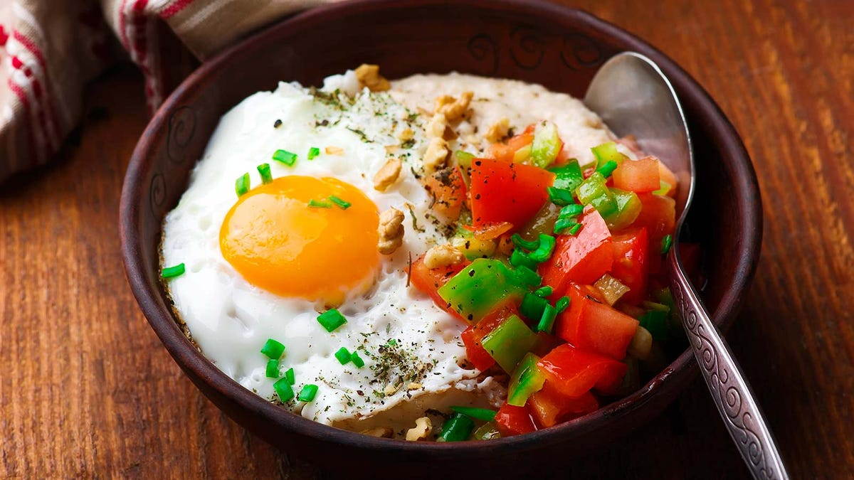 A savory bowl of oatmeal, loaded with a fried egg, cheese, and chopped peppers.