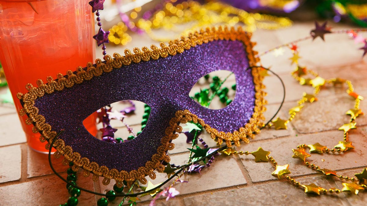 A purple and gold Mardi Gras mask resting against a cocktail, surrounded by beads.