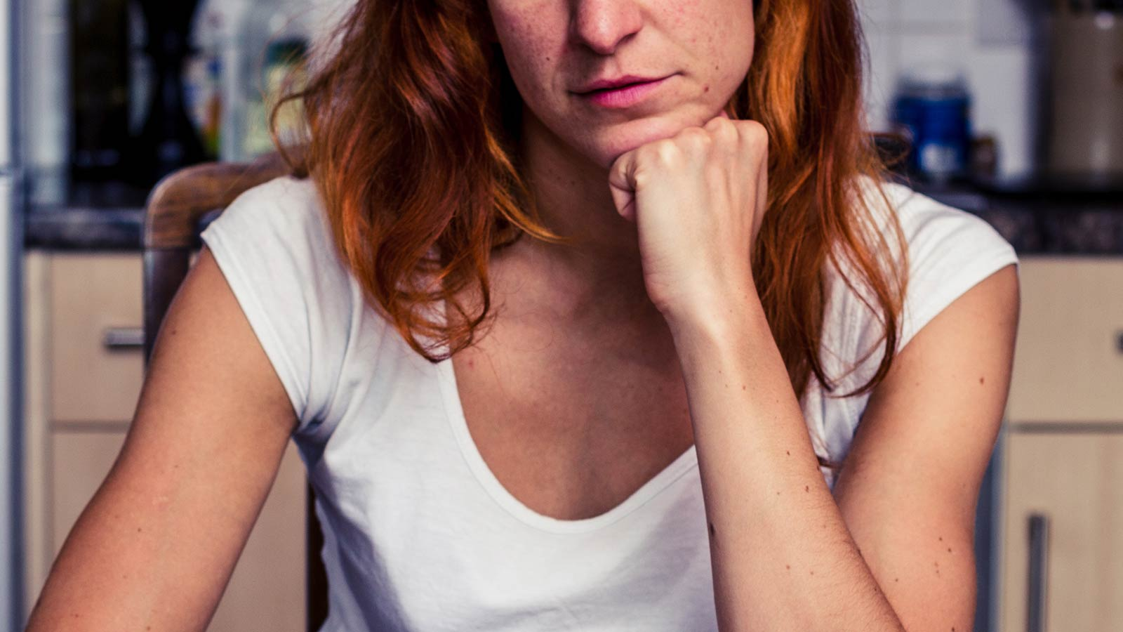 Half a woman's face, as she sits at a kitchen table, resting her chin on her hand.