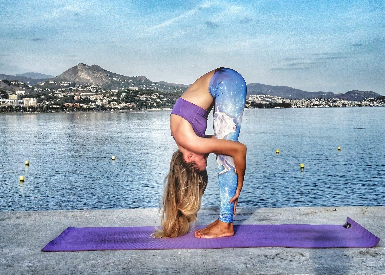 A woman doing a forward fold on a yoga mat by the sea.