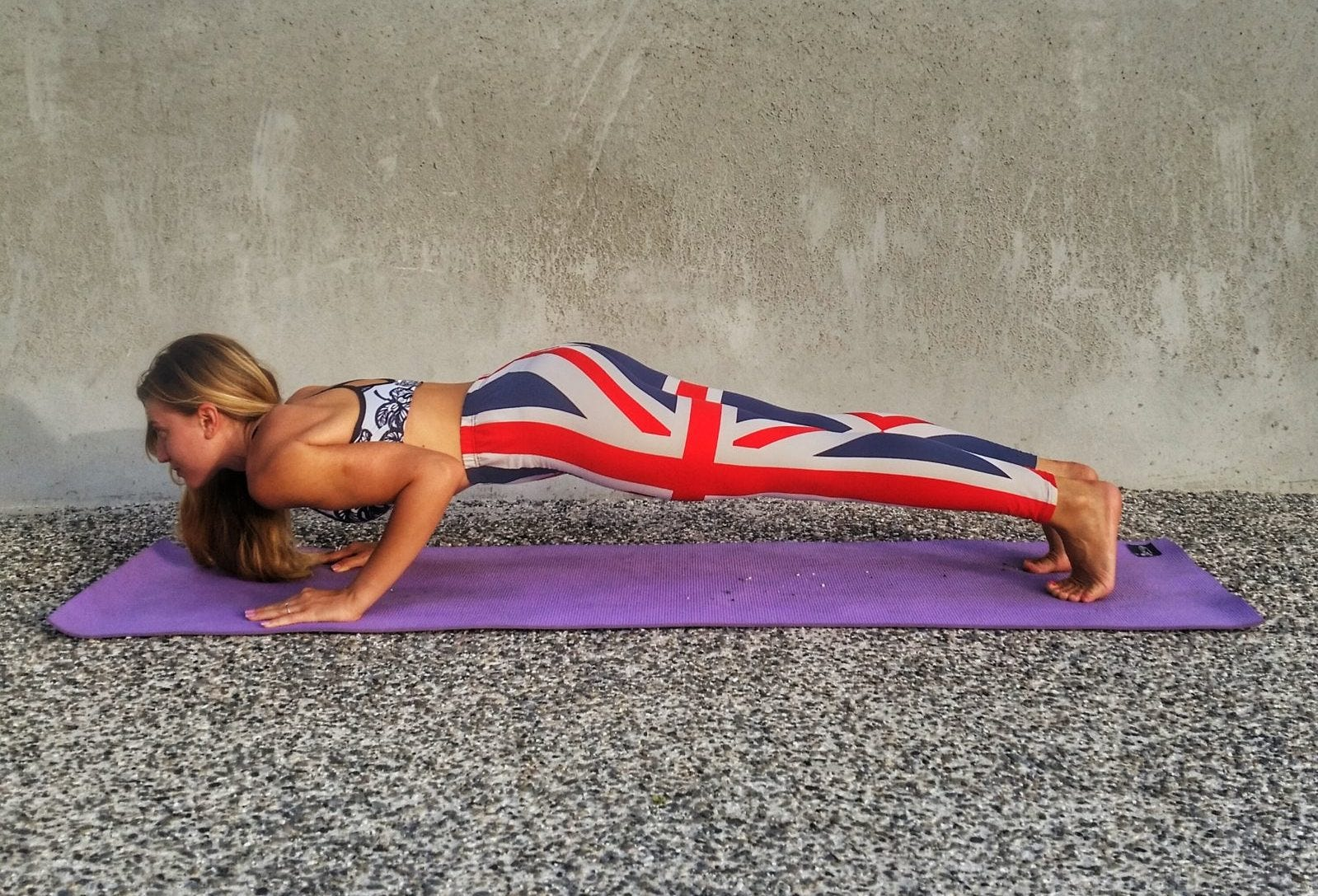 A woman on a yoga mat in a four-limbed plank pose.