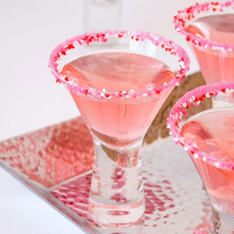 Three pink Cosmopolitan martinis with pink- and red-sugared rims.