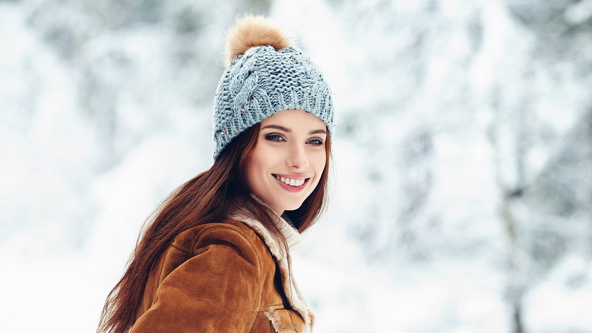 Woman with glowing healthy skin outside in a hat and coat enjoying the winter.