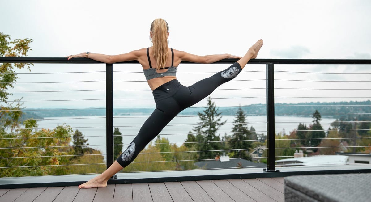 Woman doing a split on a fence