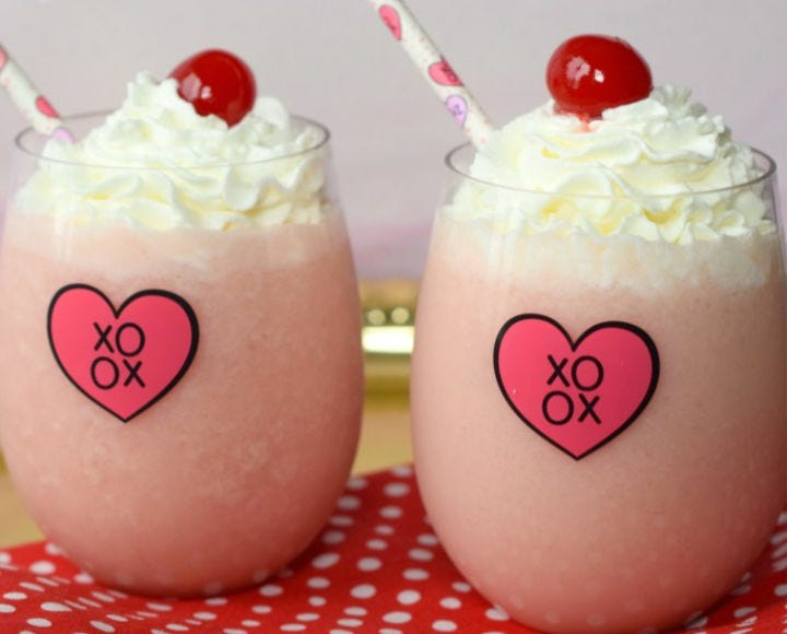 Two Cupid's Coladas in sifters with straws, each topped with whipped cream and a cherry.