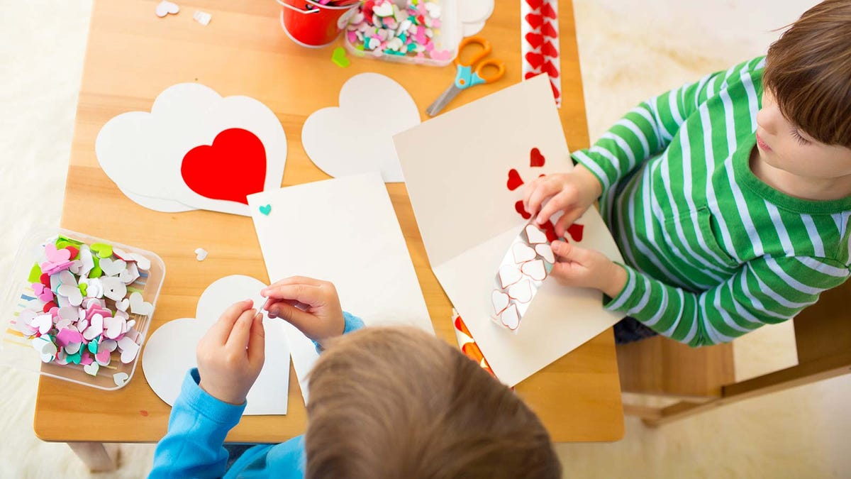 Two children working on Valentine's day cards with sticker hearts and colored pencils.