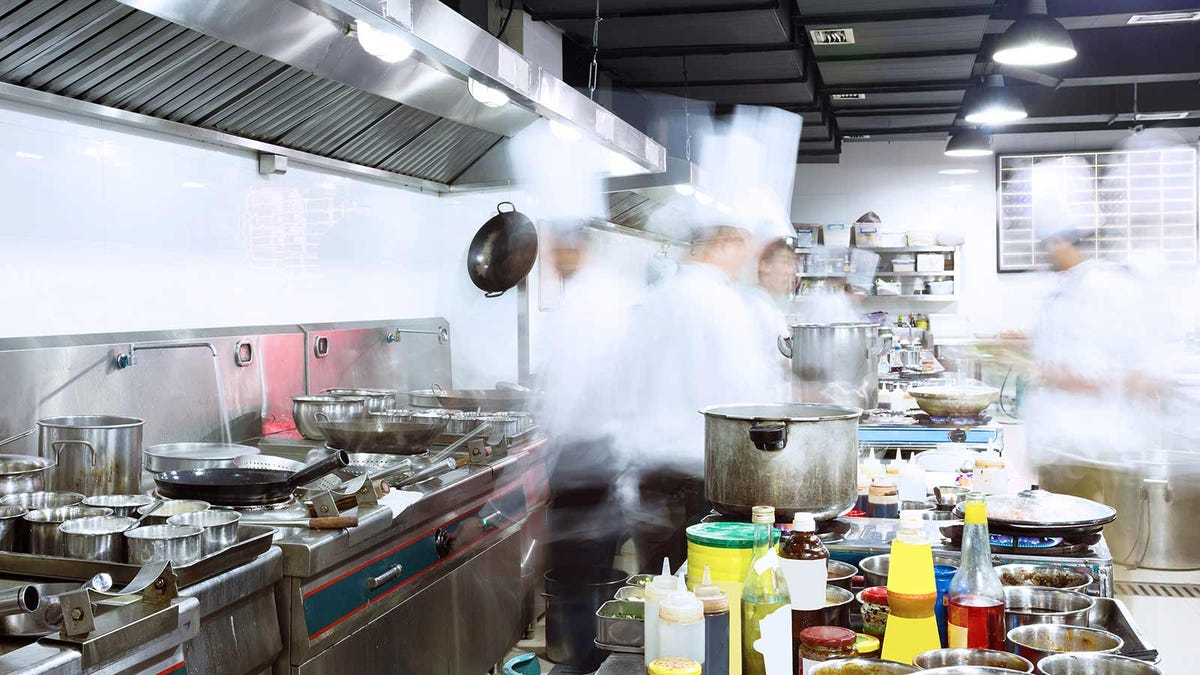 A long exposure of chefs rushing about a kitchen, preparing food.