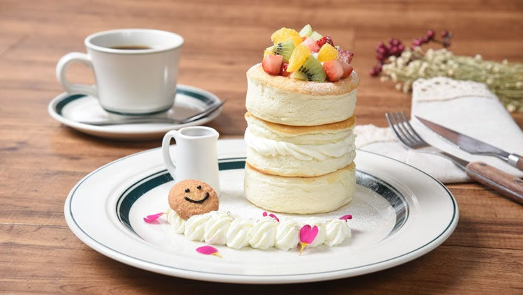 A Smile Pancake covered in fruit on a plate next to a coffee mug at the Gram Cafe and Pancakes restaurant.