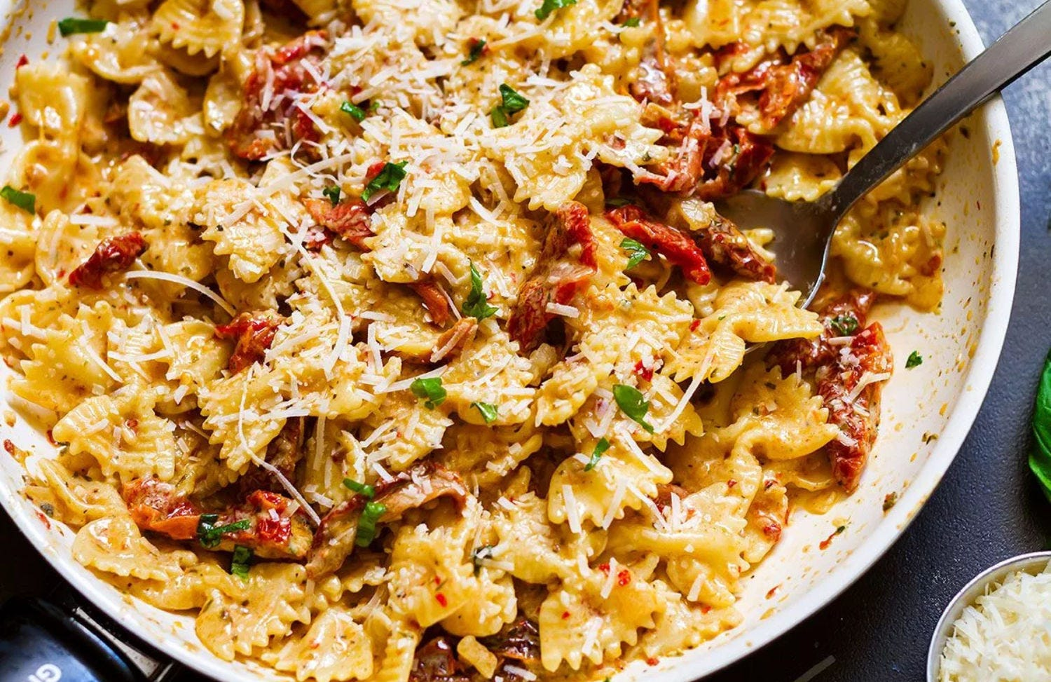 Sun dried tomato pasta in a skillet topped with grated Parmesan cheese.