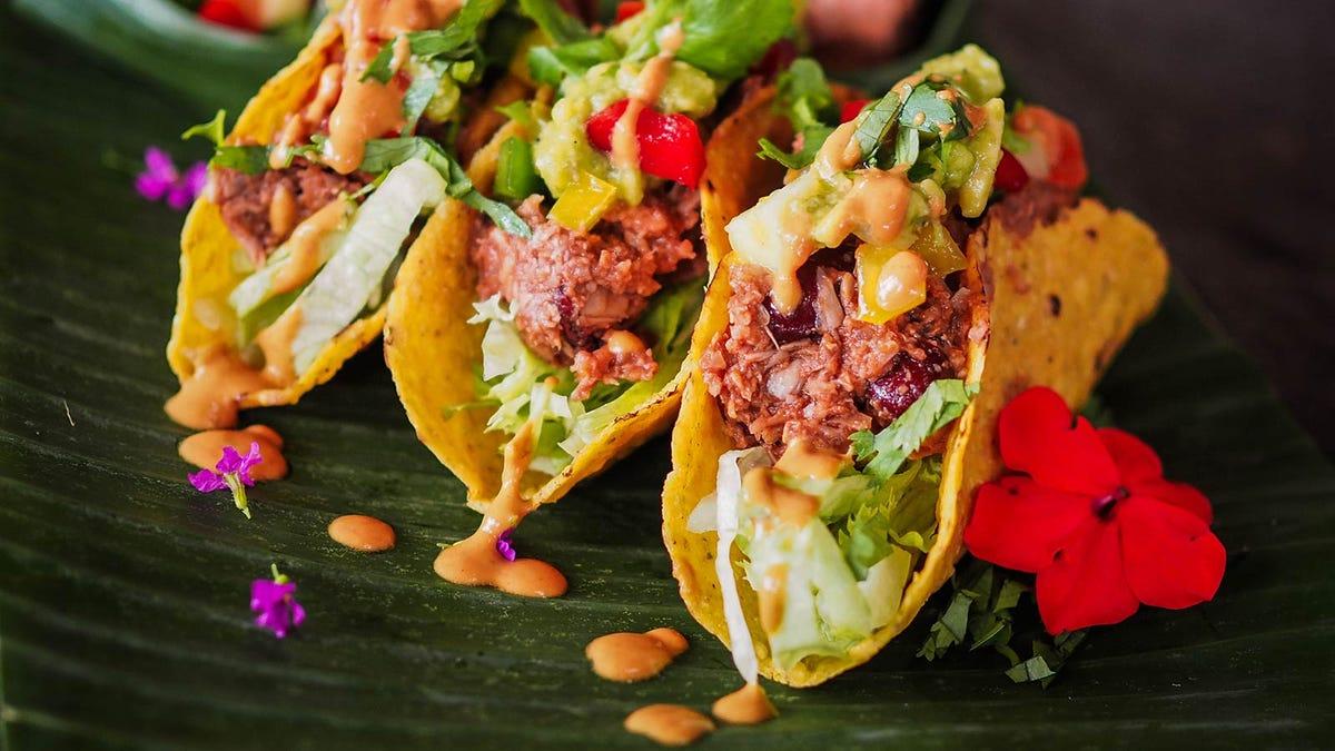 Vegan jackfruit tacos on a wooden platter.