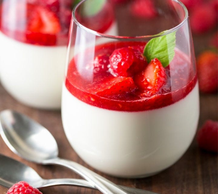 Two stemless wine glasses filled half-way with Panna Cotta and topped with fresh berry coulis and a mint leaf.