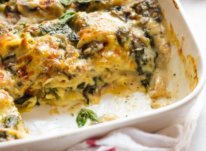 A white casserole dish filled with mushroom, chicken, and spinach lasagna.