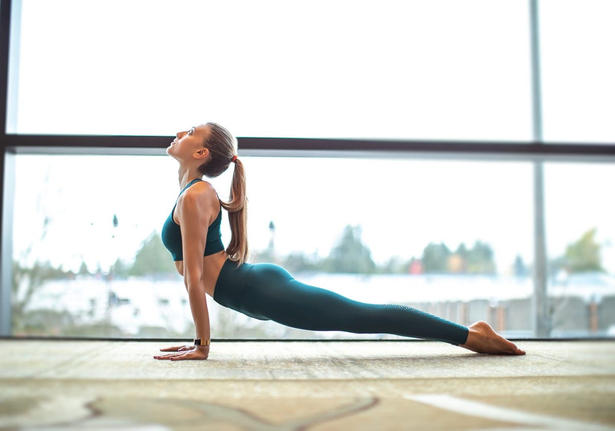 A woman in the upward-facing dog yoga pose in front of a large window.