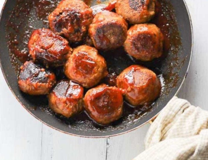 A skillet with multiple lentil bbq meatballs seared to perfection.