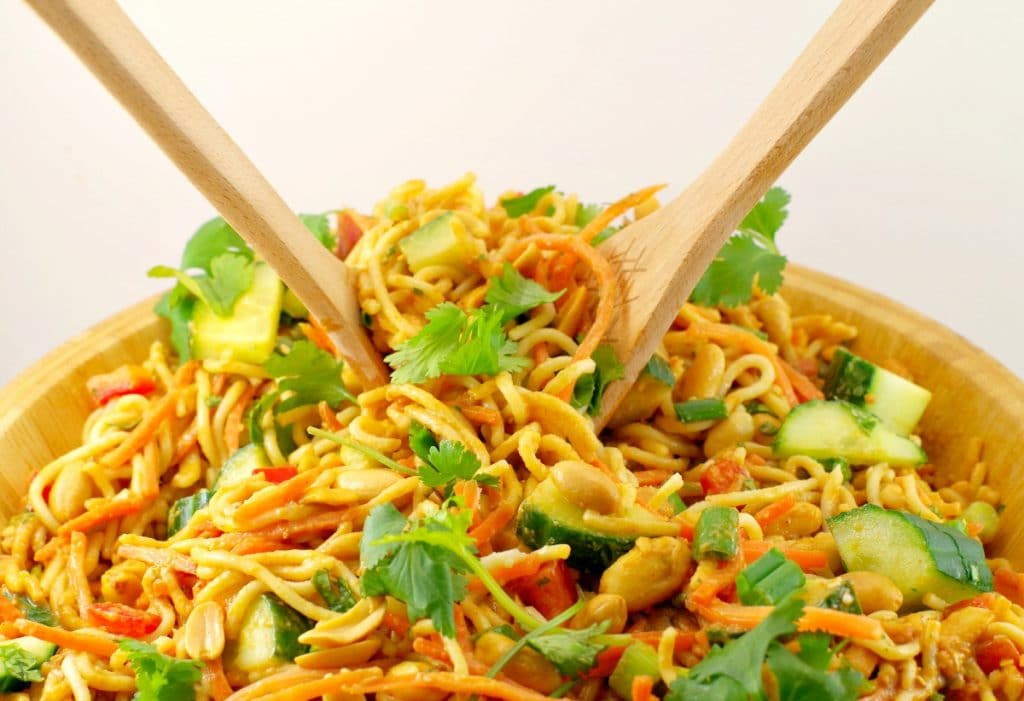 Two wooden salad spoons holding some peanut vegan pasta salad over a wooden bowl filled with it.