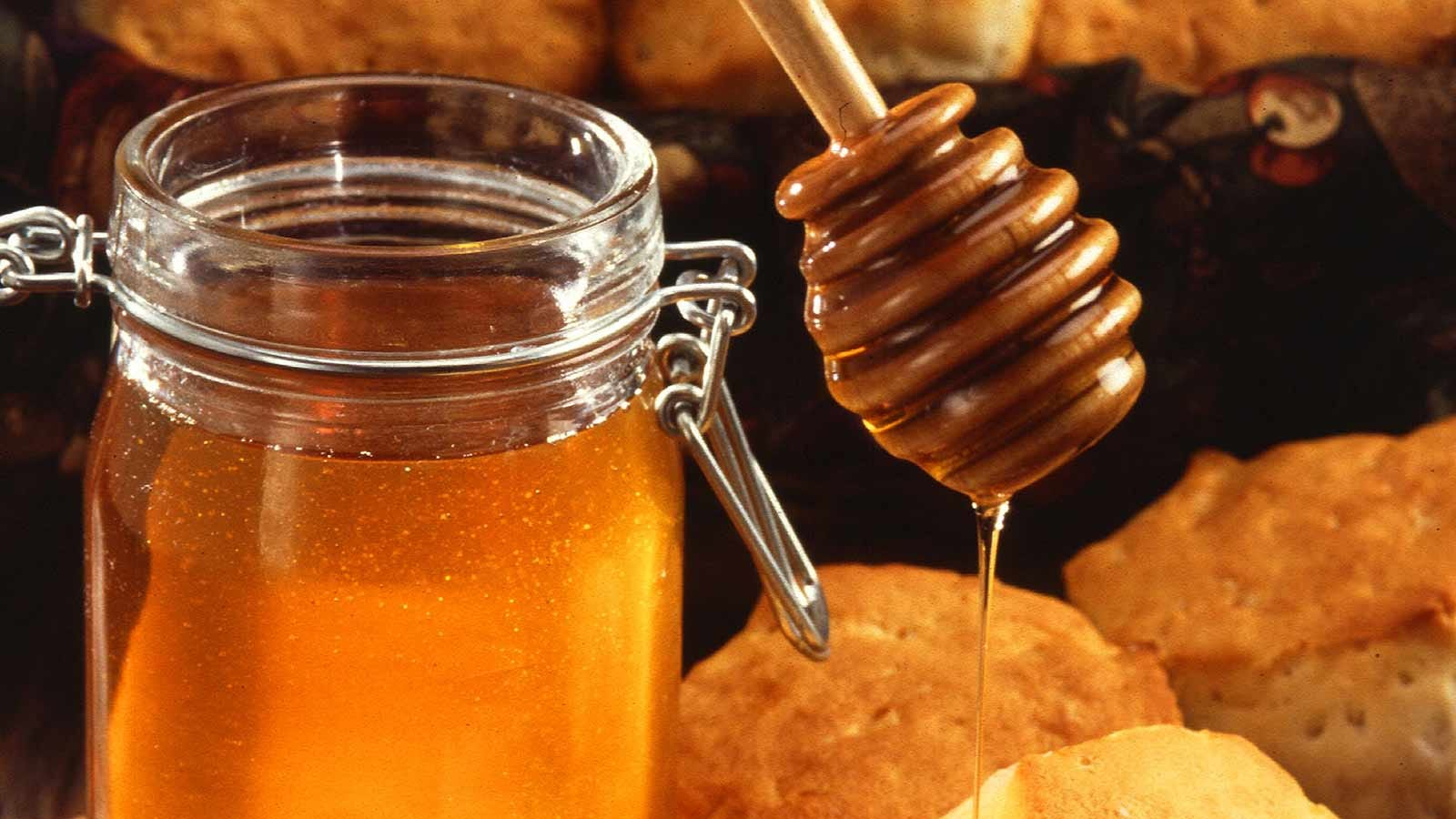 Jar of golden honey with a drizzle wand loaded with honey beside it.