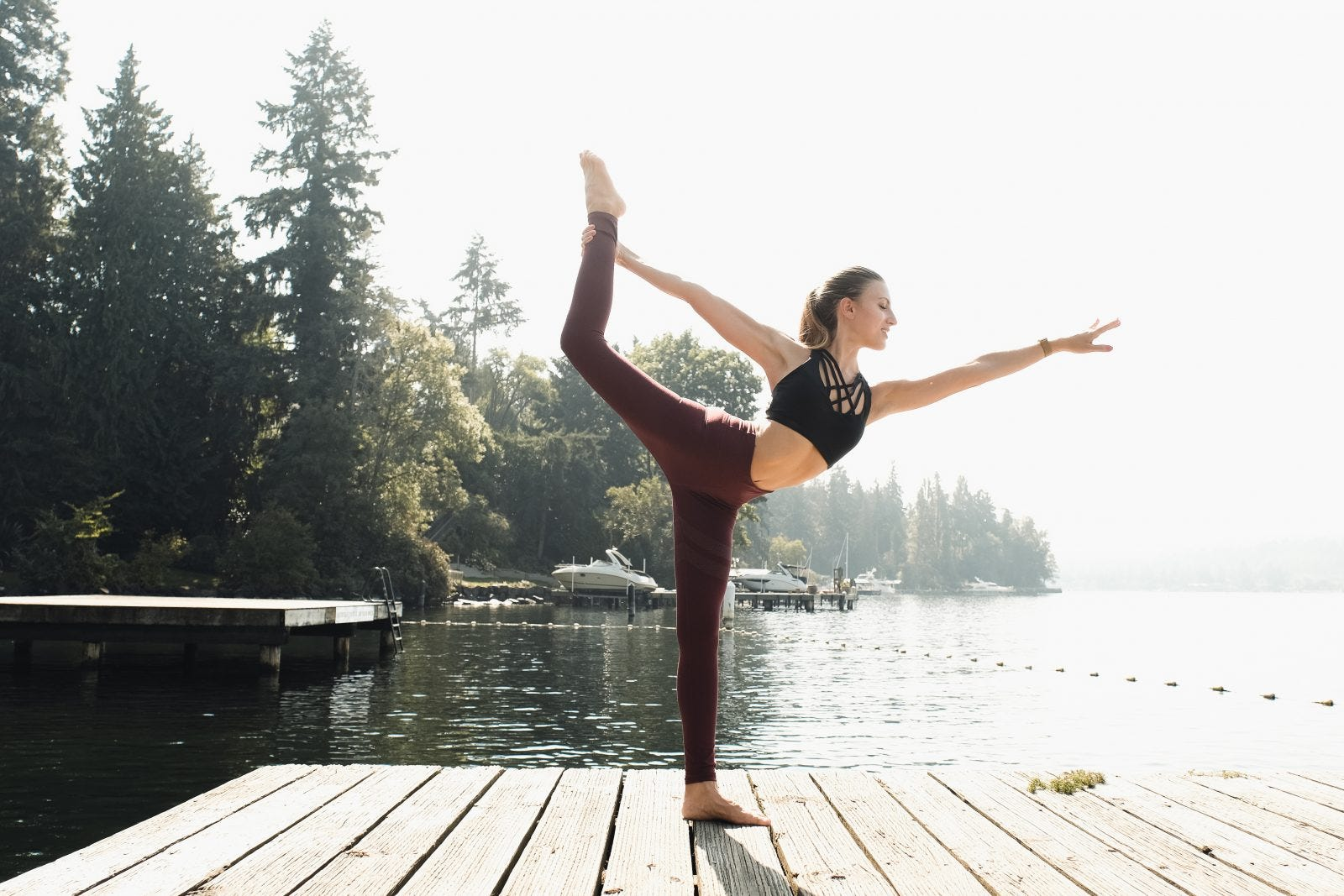 A woman in dancer's yoga pose on a deck in front of a lake.