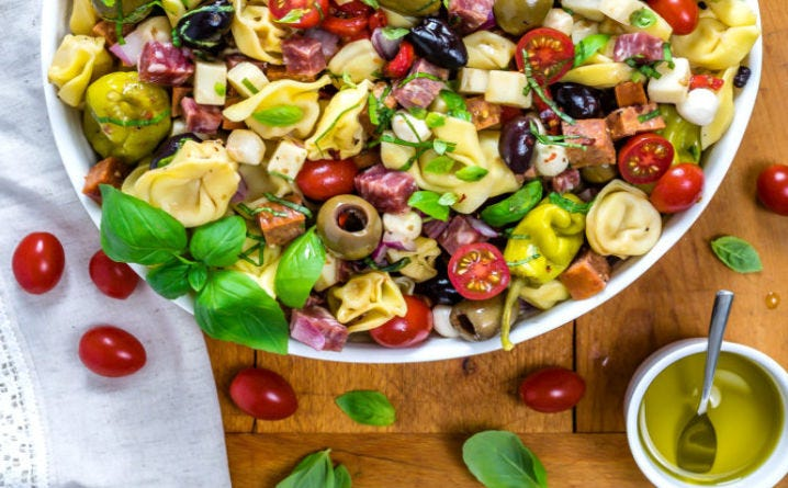 A large bowl of tortellini pasta salad on a cutting board surrounded by cherry tomatoes and a small container of extra virgin olive oil.