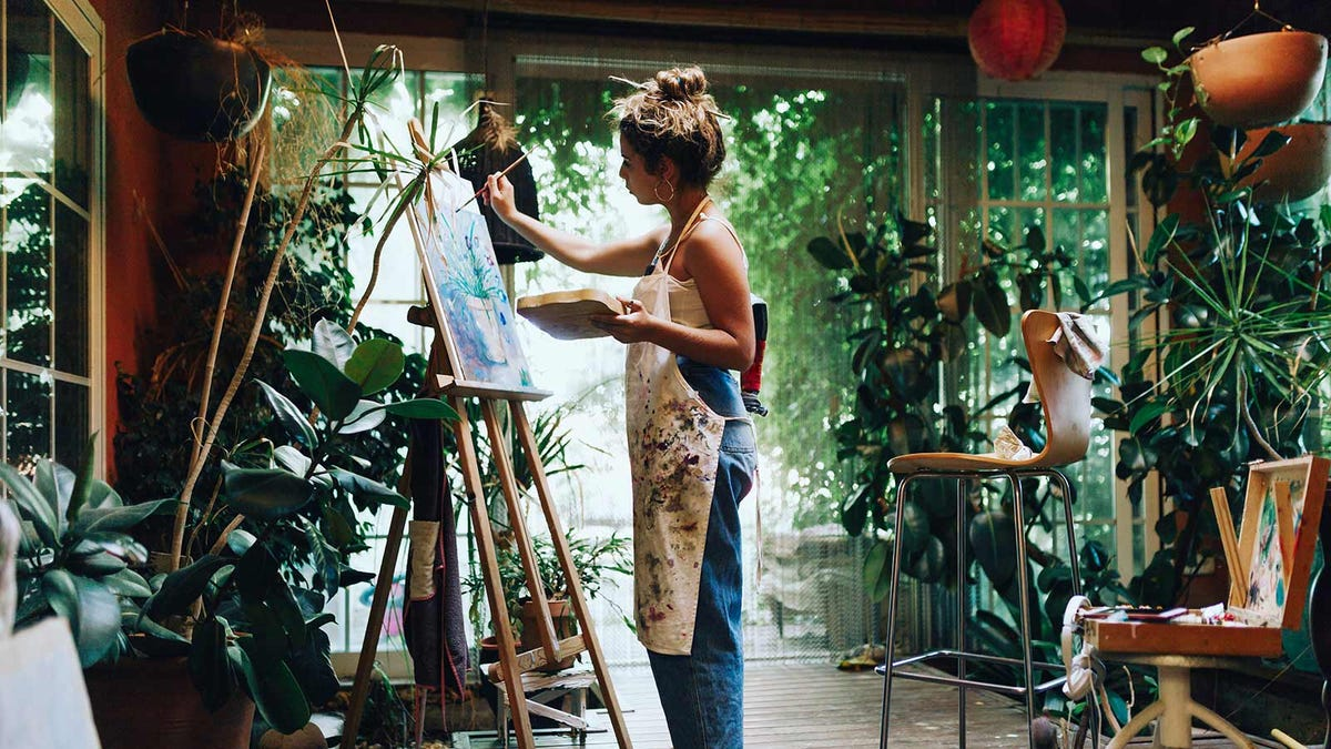 A woman painting on a canvas propped on an easel.