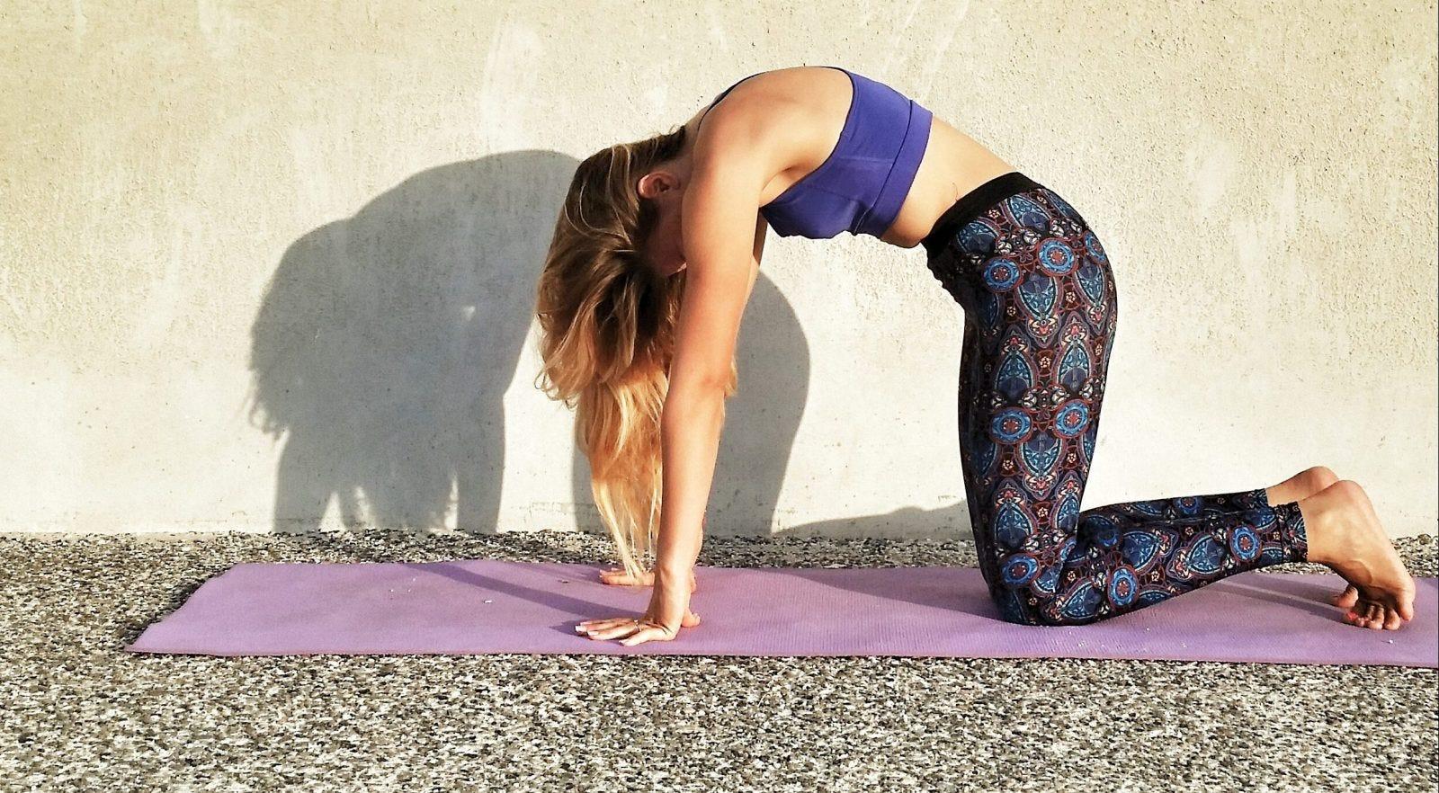 Woman doing cat pose in yoga